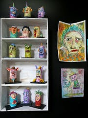 Dawna Magliacano's tubers are characters sculpted around discarded toilet paper rolls, set on a shelf next to some of her whimsical illustrations.