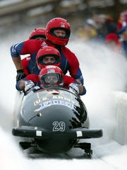 Brian Shimer, front, drives past the finish line as his teammates Mike Kohn, Doug Sharp, and Dan Steele stretch to see their time at the Utah Olympic Park, Saturday, Dec. 29, 2001, in Park City, Utah. The team finished second, good enough to put Shimer on the Olympic team. (AP Photo/Steve C. Wilson)