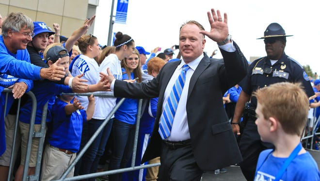 Kentucky head coach Mark Stoops greets the crowd as he and the team arrive before the game against Missouri Saturday night at Commonwealth Stadium. Sept. 26, 2015