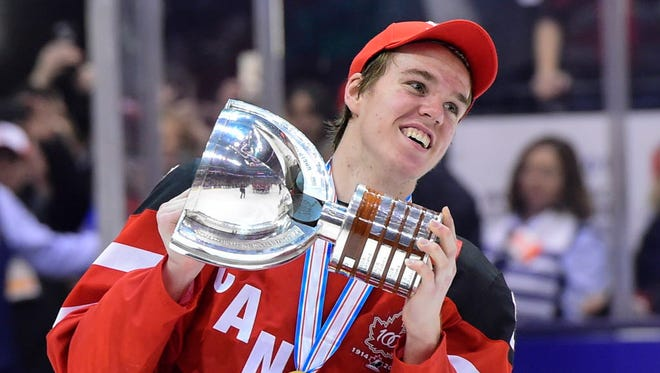 Canada's Connor McDavid skates with the trophy following his team's 5-4 win over Russia in the 2015 World Junior title game.