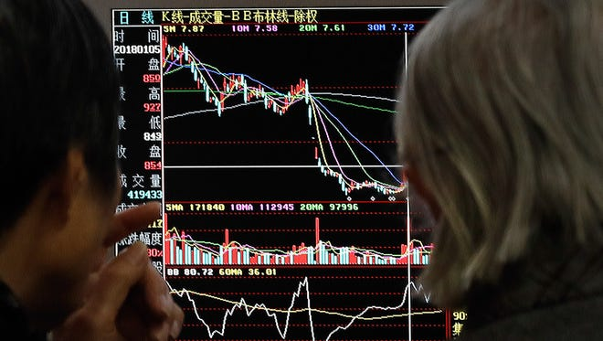 People monitor stock prices at a brokerage house in Beijing in January. As the U.S. stock market climbs further into record territory, investors are increasingly putting money on a relatively less expensive alternative: funds that own international equities.