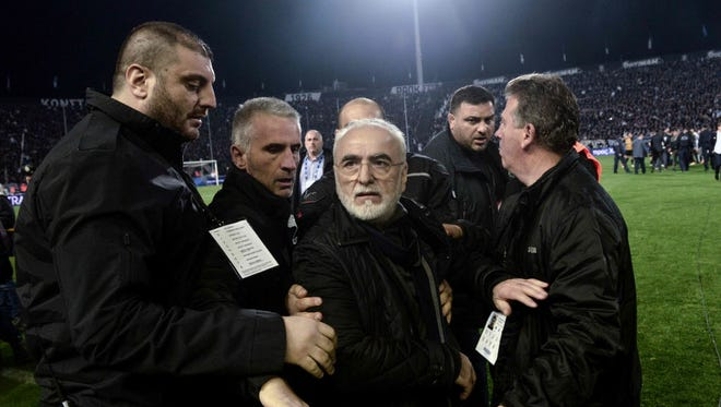 PAOK's president Ivan Savvidis  is escorted out after taking to the pitch carrying a handgun in his waistband.