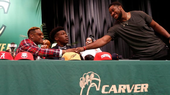 Feb 3, 2016; Montgomery, AL, USA; Carver high school linebacker Lyndell Wilson shakes hands with Alabama linebacker Shaun Hamilton (20) as he waits to make his decision at Carver High School. Mandatory Credit: Butch Dill-USA TODAY Sports ORG XMIT: USATSI-264744 ORIG FILE ID:  20160203_jdm_db7_068.jpg
