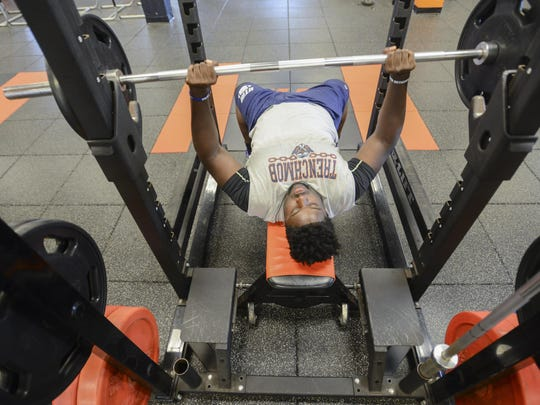 Damani Taylor, a football player at UTM, lifts weights