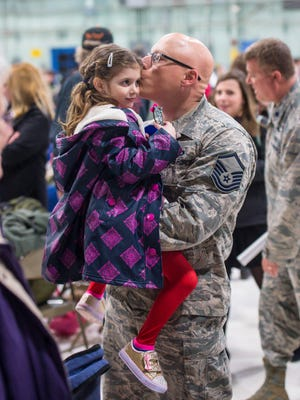 Master Sgt. Darren Adams of Milton kisses his daughter Brooke, 6, after he and more than 200 members of the Vermont Air National Guard returned to the airbase at the Burlington International Airport in South Burlington on Thursday, February 23, 2017, after a three-month deployment to the Middle East.