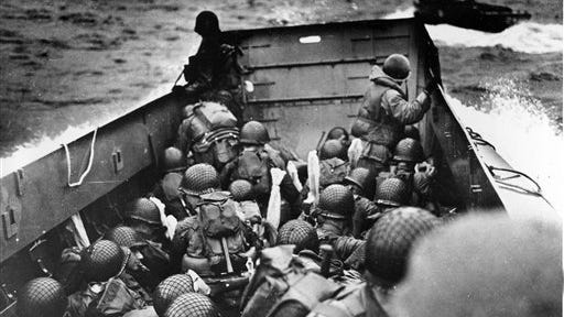 Allied troops crouch behind the bulwarks of a landing craft as it nears Omaha Beach during the June 6, 1944, D-Day landing in Normandy, France.