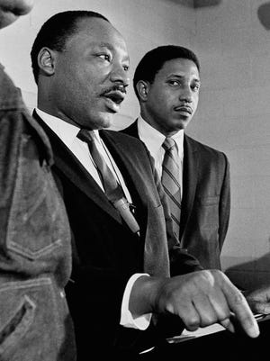 Rev. Bernard LaFayette (right), listens as Dr. Martin Luther King Jr. tells an Atlanta news conference Jan. 16, 1968, that his planned march on Washington in April to demand jobs and income for the poor will be led by 3,000 nonviolent demonstrators. Rev. LaFayette is coordinator of the march. (AP Photo/Charles Kelly )