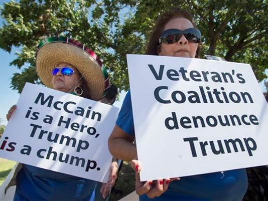 Lourdes Galvan, left, and Irma Vargas, both of San Antonio, Texas, hold signs denouncing Republican presidential contender Donald Trump, Thursday, July 23, 2015, at Laredo International Airport in Laredo, Texas. (AP Photo/Darren Abate)