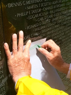 Dan Reid of Schofield makes an etching in May 2016 of the name of Michael P. Malueg on the Vietnam Veterans Memorial in Washington, D.C., as part of Never Forgotten Honor Flight.