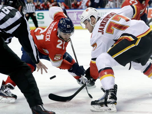 Florida Panthers' Vincent Trocheck (21) and Calgary Flames' Mark Jankowski (77) go for the puck during a faceoff during the second period of an NHL hockey game Friday, Jan. 12, 2018, in Sunrise, Fla. (AP Photo/Lynne Sladky)