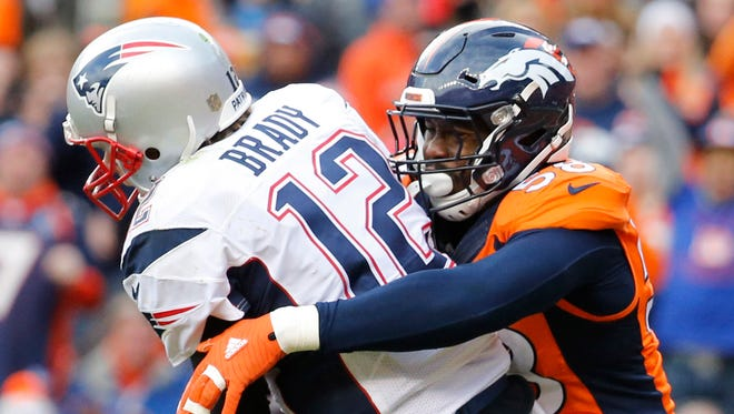 New England Patriots quarterback Tom Brady (12) is tackled by Denver Broncos outside linebacker Von Miller (58) in the third quarter in the AFC Championship football game at Sports Authority Field at Mile High.