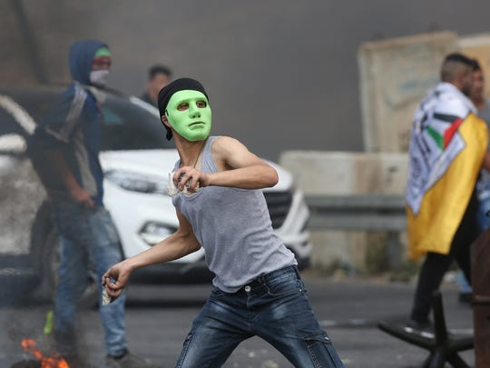 A Palestinian protester throws stones during clashes with Israeli troops after a protest against the US Embassy move to Jerusalem and ahead of the 70th anniversary of Nakba, at Huwwara checkpoint near the West Bank City of Nablus on May 15, 2018.