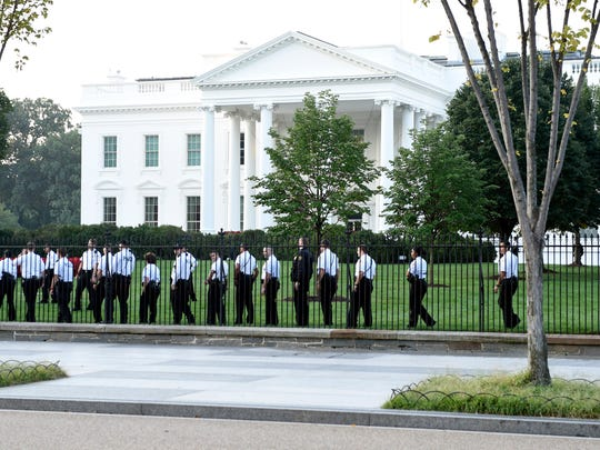 Uniformed Secret Service officers walk along the fence on the North side of the White House in Washington, Saturday, Sept. 20, 2014.  The Secret Service is coming under renewed scrutiny after a man scaled the White House fence and made it all the way through the front door before he was apprehended.