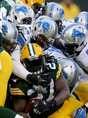 Lions defenders stop the Packers running back Eddie Lacey at the goal line during the first half on Sunday in Green Bay, Wis.