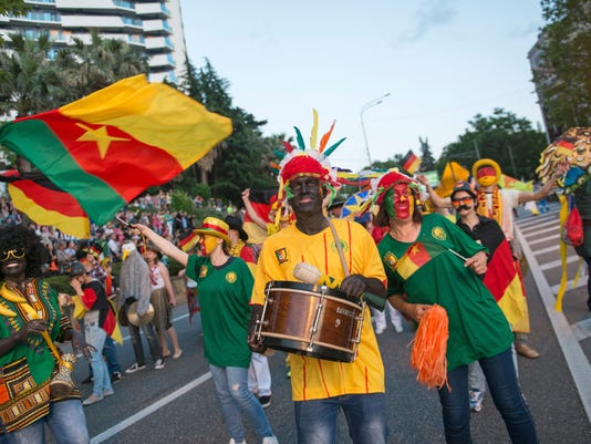 In this photo taken on Saturday, May 27, 2017 people carrying a Cameroon flag, take part in a parade in the Black Sea resort of Sochi, Russia. (AP Photo/Artur Lebedev)