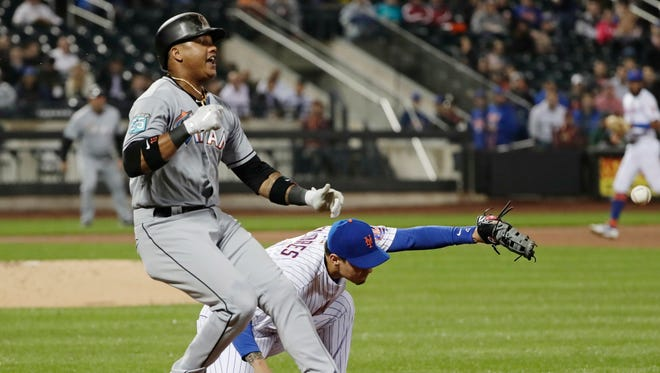 Miami Marlins' Starlin Castro (13) is safe at first base as New York Mets third baseman Wilmer Flores loses control of the ball during the fifth inning of a baseball game Tuesday, May 22, 2018, in New York. Castro advanced to second base on a throwing error by shortstop Jose Reyes.