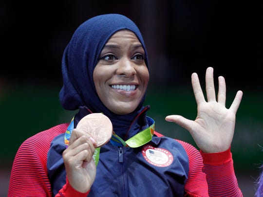 Maplewood native Ibtihaj Muhammad poses on the Olympic podium after the women's team sabre fencing event at the 2016 Summer games in Rio de Janeiro, Brazil. (AP Photo/Vincent Thian)
