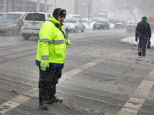 Brighton crossing guard Michael Pollock mans one of the Twelve Corners intersections during Wednesday's snowstorm.