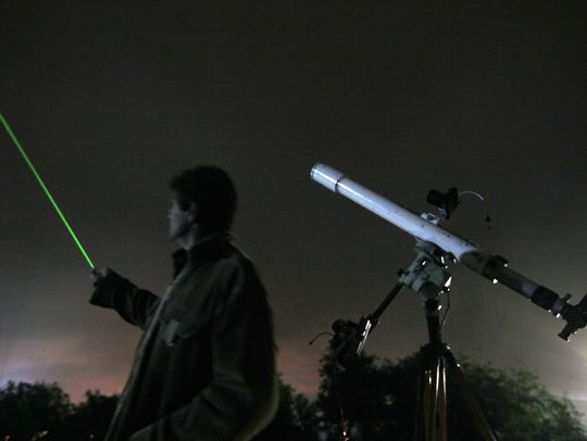 An astronomer uses a laser pointer to show the radiant