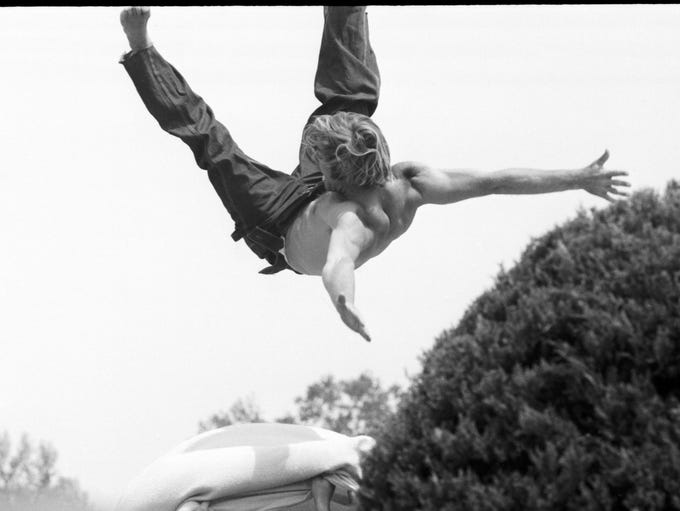A young man flies through the air during a day in the