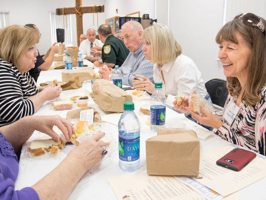 Susan Suggs, right, and others eat their brown bag meals during the Lunch Behind Bars event hosted by Pathways for Change at the Cantonment Work Camp in Pensacola on Thursday, October 27, 2016.