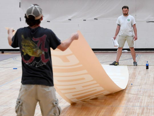 Landon Cook (left) and Cory Hughes with Hughes Flooring Designs out of Prattville, Ala., position a mask as the Meeks Family Fieldhouse inside the University of Evansville's Carson Center gets a $725,000 upgrade Tuesday, July 18, 2017.