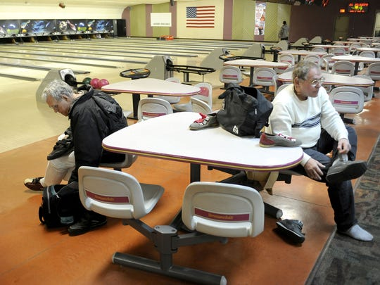 Bobby Yowell, left, and his roommate Gary Kiracofe put on bowling shoes during on an outing to Staunton Bowling Lanes on Thursday, Jan. 20, 2011. Yowell and Kiracofe grew up in institutions for mentally disabled people, and then moved together in an apartment in Staunton.