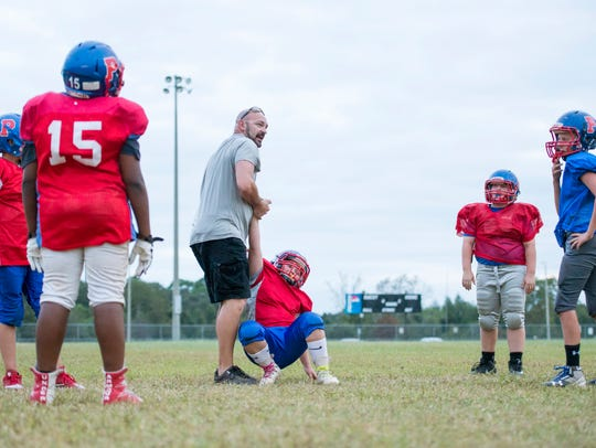 Coach Bubba Porter, center, helps a player stand up