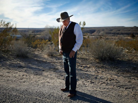 In this Jan. 27, 2016, file photo, rancher Cliven Bundy stands along the road near his ranch in Bunkerville, NV. The Nevada rancher freed from federal custody this week after his prosecution on conspiracy and assault on government officer charges collapsed is casting himself as having fought the law and winning.