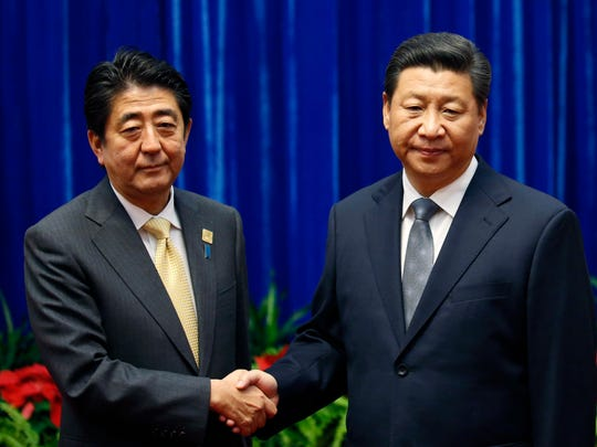 Japan's Prime Minister Shinzo Abe, left, and China's