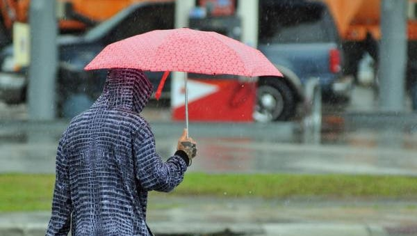 FILE - A random act of kindness. A passing motorist stopped and gave this man walking along Park Ave in Titusville an umbrella during a downpour in January, 2016.