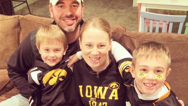 University of Iowa grads John and Lara Plaisance of Waukee hope to expand statewide the nonprofit group they founded in the name of their late son, Drew. With them in this Hawkeye family photo are sons Theo, at left, and Ben.