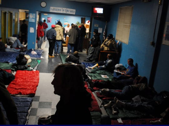 Homeless men and women claim their sleeping bags inside The Well Tuesday night on Olivier St. in Lafayette. The Outreach Center, normally only open for day use, was made available as a shelter from freezing temperatures overnight.