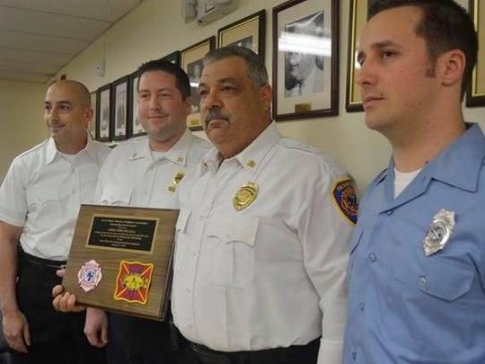 Fanwood Fire Dept. Chief John Piccola, second from right, poses with his award after being honored by the Scotch Plains Volunteer Firefighters Association with the group's 2015 outstanding service award at a Fanwood borough council meeting in Fanwood, on March 21.   With Piccola are Scotch Plains Fire Dept. Capt. Joe Rodrigues, left, Battalion Chief Skip Paal, second from left, and Captain Dennis Hercel, right, who made the presentation. Piccola was honored for his many years of leadership and fostering of cooperation between the Fanwood and Scotch Plains departments.