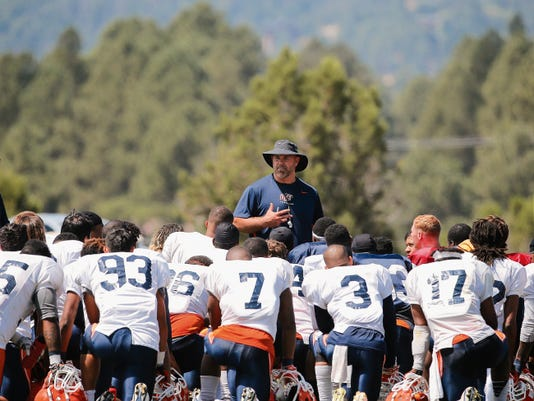 UTEP head football coach Sean Kugler talks to his team following Tuesday's scrimmage at Camp Ruidoso with the picturesque Lincoln Forest in the background.