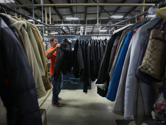 Dec. 29, 2015: Greg Schwegmann hangs freshly washed leather jackets at Sunshine Cleaners of Silver Grove, where he is part-owner. Schwegmann, who is married with to two boys, 5 and 9, credits Kalfas for keeping him off of heroin. He's been sober for the last eight years.