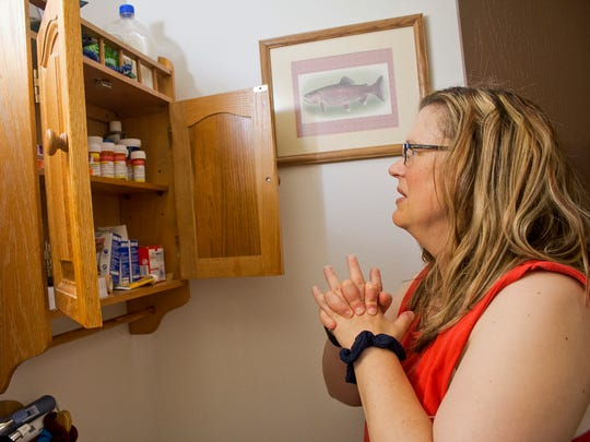 In this Wednesday, July 12, 2017, photo, Tammie Jackson looks over some of the medication that has helped her treat some of her ailments, at her home in Butte, Mont. Tammie, who was uninsured until she enrolled in Montana's expanded Medicaid program, receives medical care for a host of health issues, including a back injury that has kept from returning to her job cleaning hotel rooms. Montana officials who tout the dramatic drop in the state's medically uninsured due to expanded Medicaid, are now under pressure to reduce the number of new Medicaid enrollees.