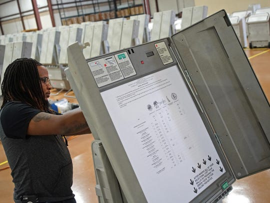 Technician James Mouzon prepares a voting machine at
