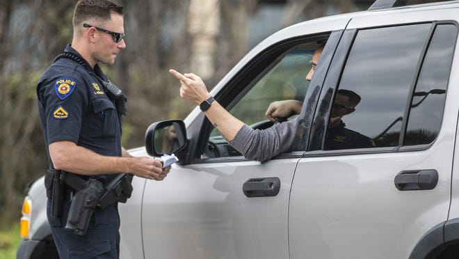 A Round Rock police officer tries to keep his social distance while making a traffic stop in March. As the pandemic worsened, officials said police received 288 coronavirus-related calls this year.