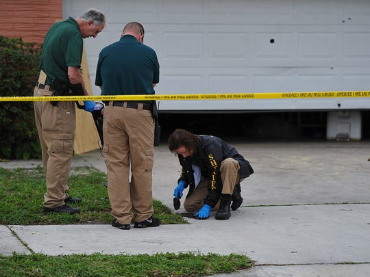 St. Lucie County crime scene investigators look for evidence at the home of Gregory Vaughn Hill Jr. in the 1500 block of Avenue Q in Fort Pierce. Hill was fatally shot by St. Lucie County Sheriff's deputies during a standoff Jan. 14, 2014.