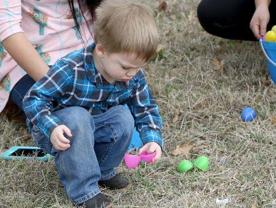 Jaxton Ballard looks inside a plastic egg Saturday,