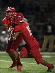 Immokalee High School's Rj Rosales hands off the ball during a game against Booker High School in Immokalee, Fla., on Friday, Nov. 10, 2017.