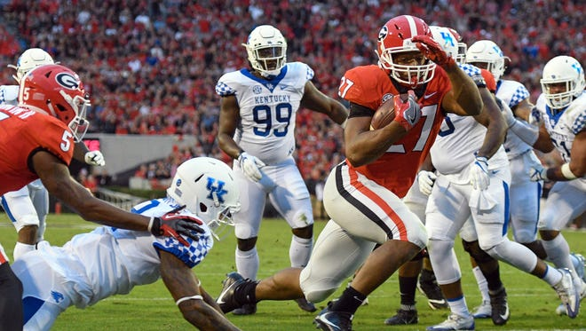 Georgia Bulldogs running back Nick Chubb (27) jumps past Kentucky Wildcats cornerback Derrick Baity (8) to score a touchdown during the first quarter at Sanford Stadium in Athens, Georgia, on Saturday, Nov. 18, 2017.