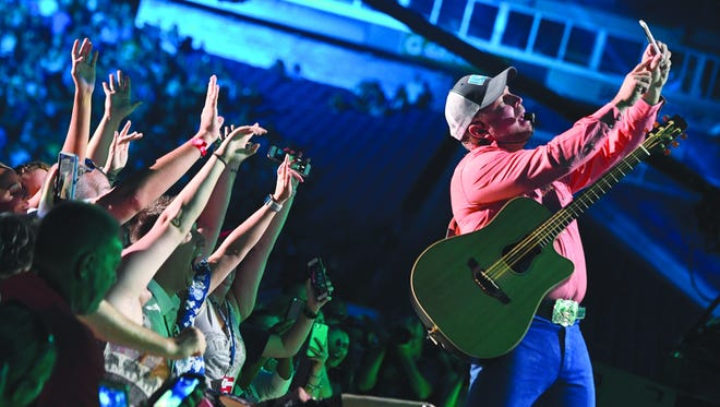 Garth Brooks takes a selfie with fans as he performs at Nissan Stadium on the first day of CMA Music Fest June 8, 2017.