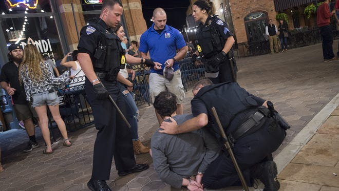 Fort Collins police detain a man who allegedly assaulted bar staff in Old Town Square on Aug. 27.