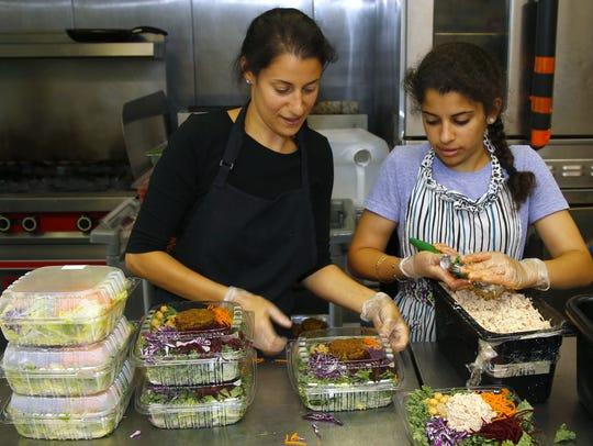 Nicole and Nina Shamah prepare an order of salad for