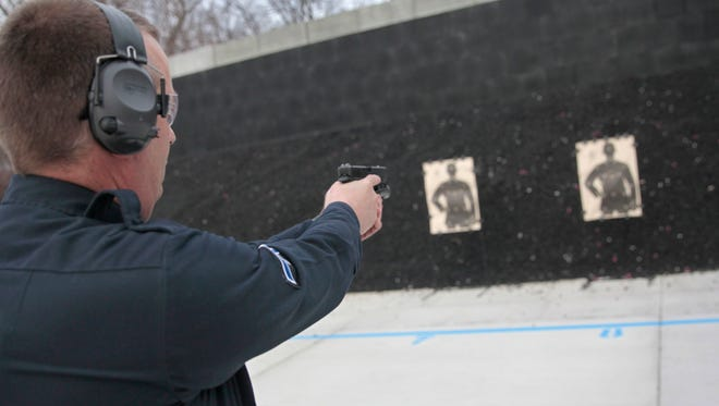 Greece Police officer Kevin McKeon makes sure his firearm is empty while at the Greece Police Department firing range Jan. 8 on Island Cottage Road.  The range was remediated and renovated using money from the equitable sharing program with Department Of Justice.
