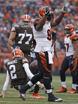 Bengals defensive end Wallace Gilberry shows the money sign after sacking Browns quarterback Johnny Manziel in the first quarter at FirstEnergy Stadium.