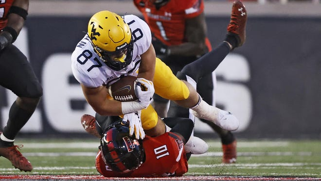 West Virginia's Mike O'Laughlin is tackled by Texas Tech's Cam White during their game in Lubbock on Oct. 24. The Mountaineers play at Texas this week.