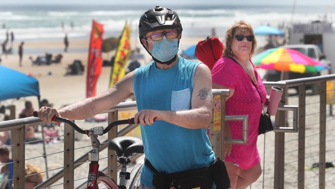 A bicyclist heads for the beach wearing a surgical face mask in March at the Flagler Avenue Beachfront Park in New Smyrna Beach during the cornoavirus outbreak.